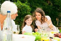 Grande famille ayant un pique-nique dans le jardin Images libres de droits