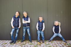 Grande famille caucasienne drôle de trois frères et de soeur posant la position sur le fond de croissance du mur dans la pleine c photo libre de droits