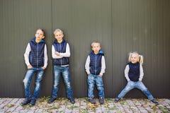 Grande famille caucasienne drôle de trois frères et de soeur posant la position sur le fond de croissance du mur dans la pleine c image stock