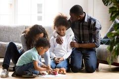 Grande famille d'Afro-américain jouant ensemble sur le plancher chaud images libres de droits