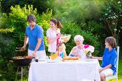 Grande famille heureuse appréciant le gril de BBQ dans le jardin Photos libres de droits