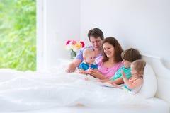 Grande famille heureuse dans un lit Images stock
