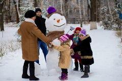 Grande famille heureuse : le père, les filles et la grand-mère sculptent un grand vrai bonhomme de neige image libre de droits