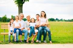 Grande famille s'asseyant sur un banc Photographie stock