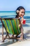 Grande femme principale s'asseyant sur une chaise de plate-forme sur la plage de mer Photos stock