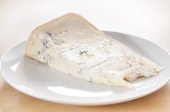 Grande fetta di formaggio fresco di Gorgonzola sul piatto ceramico bianco fotografia stock