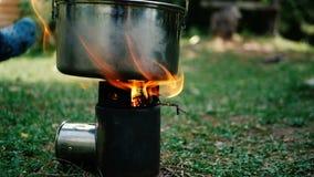 Grande fiamma sopra un piccolo forno con una casseruola nelle montagne georgiane nel slo-Mo stock footage