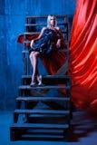 Grande fille avec les cheveux blancs se reposant sur des escaliers et regardant au photo libre de droits