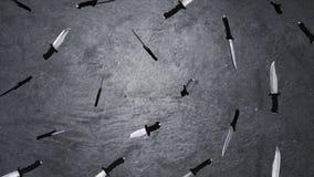 Grande fin de lame de couteaux sur le fond gris Animation des couteaux de vol Le concept de l'un grand nombre Photographie stock libre de droits