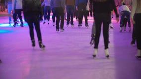 Grande folla dei giovani che pattinano sulla pista di pattinaggio sul ghiaccio dell'interno con ghiaccio fabbricato e su luce col archivi video