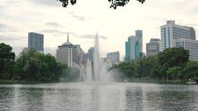 Grande fonte no fundo dos arranha-céus Arquitetura urbana bonita com um grande lago e umas plantas verdes video estoque