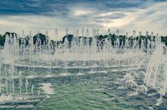 Grande fonte no parque no fundo de árvores verdes e foto de stock