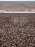 Grande forma do coração do amor feita com os seixos na praia Colheita vertical foto de stock royalty free
