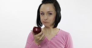 Grande, fra?che et juteuse pomme rouge de jeune belle consommation de femme sur le fond blanc banque de vidéos