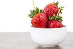 Grande fraise à l'arrière-plan blanc de côté droit blanc de cuvette sur le bois Photographie stock libre de droits