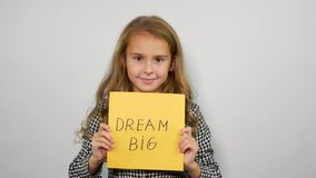 Grande frase di sogno su carta gialla Slogan sorridente della tenuta della ragazza archivi video