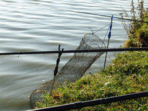 A grande gaiola da pesca abaixou na água e nas varas de pesca na margem Fotos de Stock Royalty Free