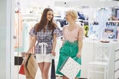 Grande giorno per comperare Due belle donne con i sacchetti della spesa che se esaminano con il sorriso mentre camminando al immagini stock