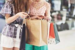 Grande giorno per comperare Due belle donne con i sacchetti della spesa che se esaminano con il sorriso mentre camminando al fotografie stock libere da diritti