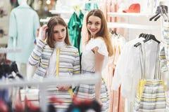 Grande giorno per comperare Due belle donne con i sacchetti della spesa che se esaminano con il sorriso mentre camminando al fotografia stock