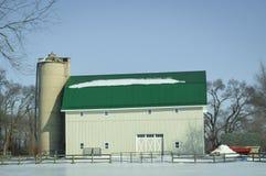 Grande granaio verde bianco del tetto con il silo nella neve di inverno fotografia stock