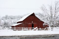 Grande grange rouge dans la neige. Photos stock