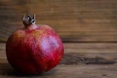Grande grenade mûre sur un fond en bois avec l'espace de copie pour le texte Fruit entier de grenade closeup Photo libre de droits