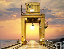 Grande grue de portique sur le coucher du soleil photos stock