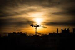 Grande grue industrielle silhouettée au coucher du soleil photos libres de droits