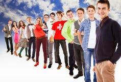 Grande grupo de adolescentes vestidos coloridos felizes no céu azul com nebuloso branco Fotos de Stock Royalty Free