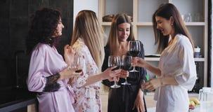 Grande grupo de sorriso de senhoras no pijamas que apreciam o partido da solteira em casa que bebe o vinho e que sente muito filme