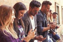 Grande gruppo di amici che per mezzo dello Smart Phone contro una parete rossa Immagini Stock Libere da Diritti