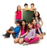 Grande gruppo di bambini e di lavagna della scuola Immagine Stock