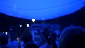 Grande gruppo di gente felice che gode del concerto rock, applaudente con le mani su sollevate, luci blu dalla fase, aria aperta stock footage