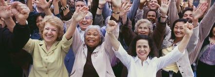 Grande gruppo di gente multi-etnica che incoraggia con le armi alzate Immagini Stock Libere da Diritti