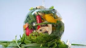 Grande gruppo di verdure su un vaso con acqua su fondo bianco video d archivio