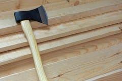 Grande hache pointue avec la lame noire et la poignée jaune-clair sur les conseils en bois frais Images libres de droits