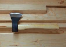 Grande hache pointue avec la lame noire et la poignée jaune-clair sur les conseils en bois frais Images stock