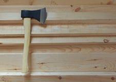 Grande hache pointue avec la lame noire et la poignée jaune-clair sur les conseils en bois frais Image stock