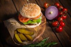 Grande hamburguer apetitoso com carne, batatas e queijo em uma superfície de madeira Fotos de Stock