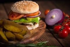 Grande hamburguer apetitoso com carne, batatas e queijo em uma superfície de madeira Imagem de Stock Royalty Free