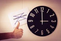 Grande horloge noire sur le mur blanc Changement de temps DST Enquête de l'Union européenne Geste de désaccord Pouces de T  photo libre de droits
