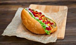 Grande hot dog saporito con salsa e le verdure in pergamena sui precedenti di legno buongustaio dell'hot dog Fotografia Stock Libera da Diritti