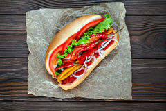 Grande hot dog saporito con salsa e le verdure in pergamena sui precedenti di legno buongustaio dell'hot dog Fotografie Stock