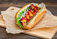 Grande hot dog saporito con salsa e le verdure in pergamena sui precedenti di legno buongustaio dell'hot dog Immagini Stock