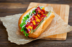 Grande hot dog saporito con salsa e le verdure in pergamena sui precedenti di legno buongustaio dell'hot dog Fotografia Stock