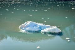 Grande iceberg e molti pezzi minuscoli che galleggiano e che si fondono fotografia stock