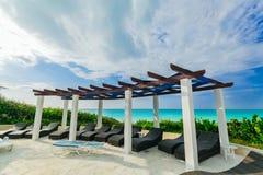Grande ideia da área de piscina dourada do hotel da tulipa com as camas confortáveis do sol perto da praia e do oceano tranquilo  Foto de Stock Royalty Free