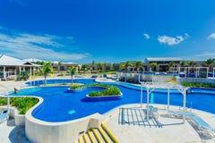 Grande ideia de convite da piscina e de terras douradas do hotel da tulipa com os povos no fundo Foto de Stock