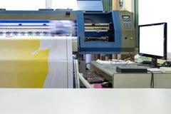 Grande impressora a jato de tinta que trabalha na bandeira do vinil com seixos do computador Foto de Stock Royalty Free